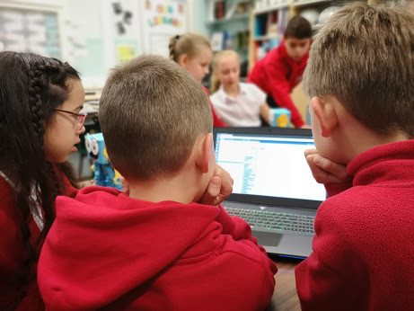 Some students around a laptop writing code with Marty the Robot